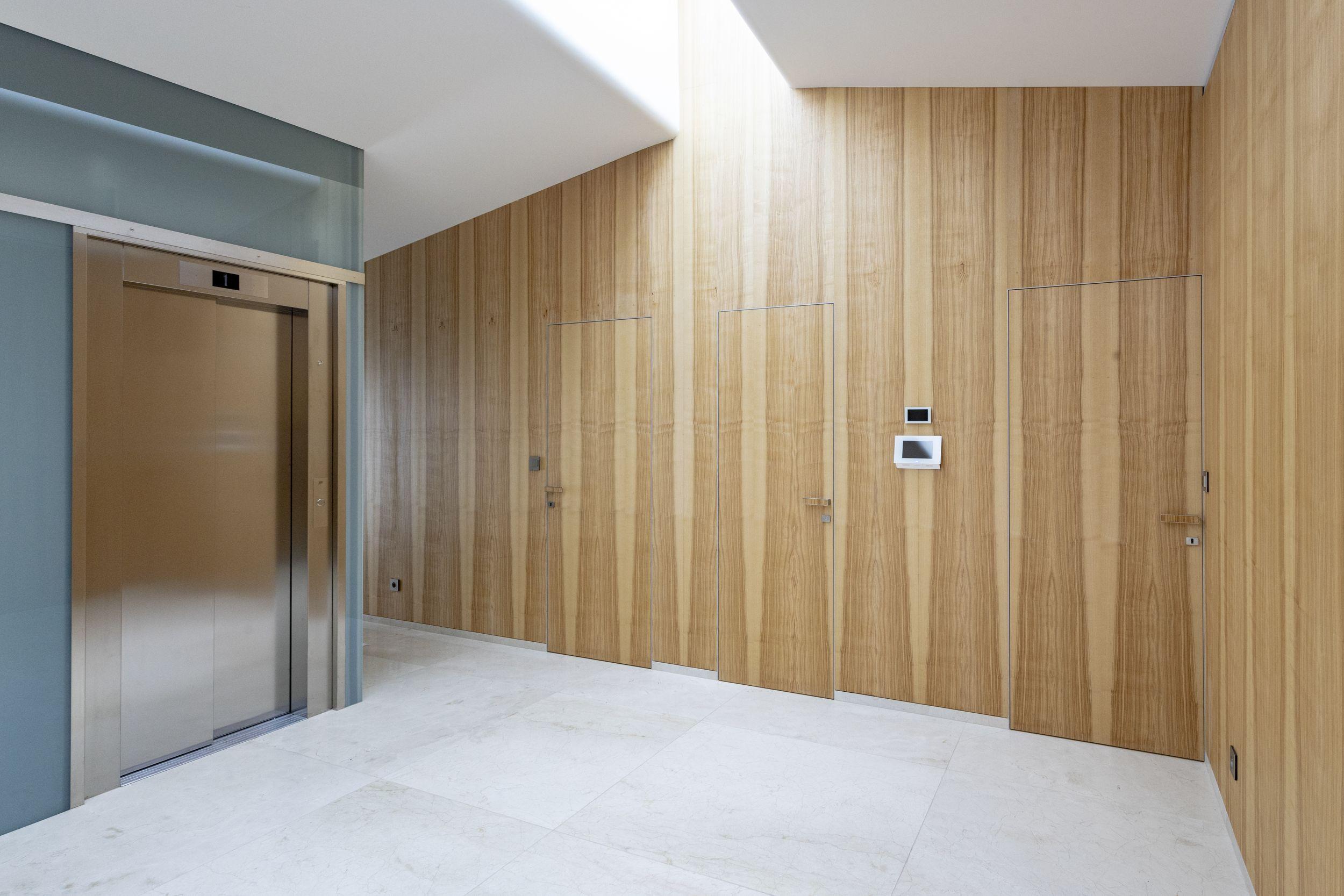 Skryté zárubně a dveře s dřevěným obkladem.